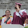 Newburyport: Senior class president Alexander Bradley hangs onto his cap in the wind as he gives the class gift to junior class president Jillian Ouellette at the Newburyport High Graduation Ceremony at War Memorial Stadium  Sunday. jim Vaiknoras/staff photoa