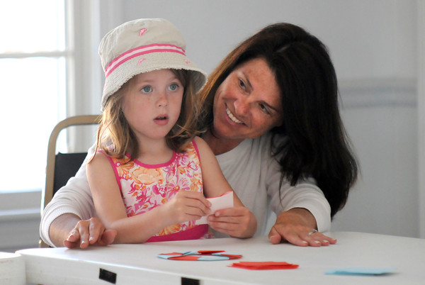 Newbury: Caroline Perry, 5, gets some help from her mom Kerri as she makes an origami sailboat at a workshop put on by Michael LaFosse at Pita Hall. The event was sponsered by the Newbury Library. Jim Vaiknoras/staff photo