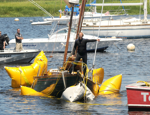 Newburyport: A crew member of TowBoat/US stands on the bow of  a wooded sailboat as it is towed to the Merri-Mar Marina in Newburyport. The boat sank in the Merrimack River off the Newburyport waterfront Sunday morning. Jim Vaiknoras/staff photo