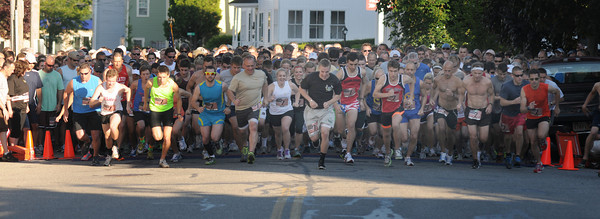 Newburyport: Twelve hundred runner take off on Merrimac street at the start of the Derek Hines Flag Day 5K. Thursday nght. Jim Vaiknoras/staff photo