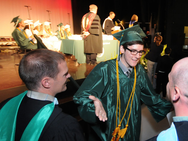 west Newbury: Liam Loenard-Solis greats his class advisers Richard Harty and Matthew Smith after getting his diploma at the Pentucket Commencement Saturday. Jim Vaiknoras/staff photo