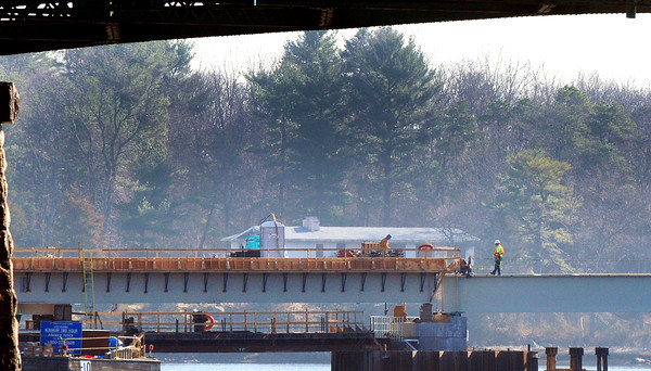 Amesbury: Contruction workers can be seen on the spans of the new Hines Bridge in Amesbury in photo taken from the Spring Lane Pumping Station in Newburyport. The old span on the north side of the bridge remains and is the last to be replaced. Bryan Eaton/Staff Photo