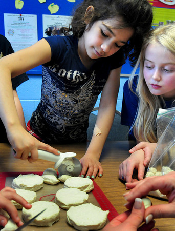 "Amesbury: Julia DiGrazi, left, looks on as Gina Kelley, both 10, cut biscuits into quarters to make ""monkey bread."" The two were in a baking class taught by Susan Lamkins, one of the PTA's afterschool programs at Amesbury Elementary School. Bryan Eaton/Staff Photo"