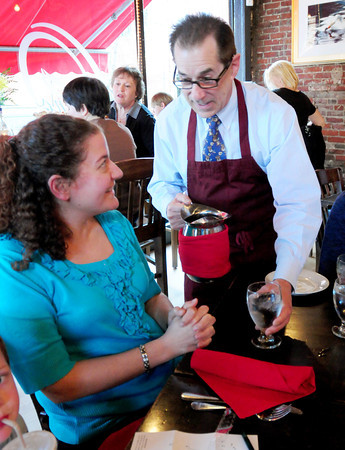 Newburyport: Newburyport Schools Superintendent Marc Kerble donned a crimson red apron as a special guest server, here serving Brown School teacher Giovanna Foster at Oregano's Restaurant. It is the third of four fundraisers there for the elementary schools netting them 20 percent of lunch and dinner on those days they're held. Bryan Eaton/Staff Photo