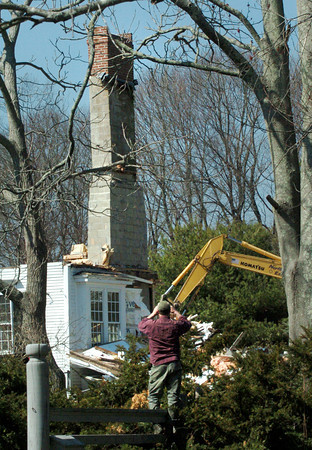 Newbury: One of a half dozen spectators watching the controversial demolition of an old home on Little's Lane takes a picture of the standing chimney. Bryan Eaton/Staff Photo