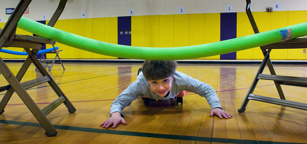 "Newbury: Parker Burns rolls under a ""noodle"" during a scooter obstacle course yesterday afternoon. The seven year-old was in Anna Molesso's physical education class. Bryan Eaton/Staff Photo"