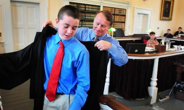 "Newburyport: Newburyport Superior Court Judge Richard Welch transfers his robe to Nock Middle School student Sean Keeley on Thursday morning. The eighth-graders at the Newburyport school have been reading to ""Kill a Mockingbird"" in their language arts class and acted out the trial as they are learning about civil rights in their social studies class. Bryan Eaton/Staff Photo"