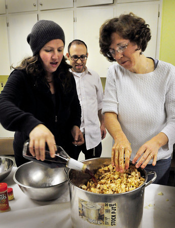 Newburyport: Rabbi Avi Poupko looks on as his wife, Carina, left, adds some wine to charoset, a traditional Passover dish, at Congregation Ahavas Achim as Rev. Martha Hubbard mixes it. Charoset is a dip used with matzo and will be served at an Interfaith Passover Seder on Sunday at 4:00 p.m. at the temple. Bryan Eaton/Staff Photo