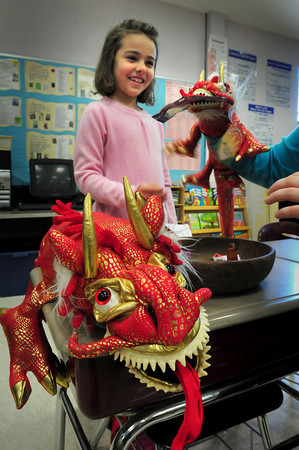 "Amesbury: Libby Waterman, 7, shows off her display items of China to fellow students at the Cashman School in Amesbury on Tuesday morning. The second-graders brought out their ""Culture Kits"" to show the research they did on their country or culture of choice. Bryan Eaton/Staff Photo"
