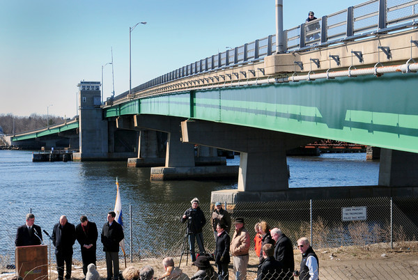 A bicyclist rides by as local and state officials and citiizens attend the official launch of the rail trail connector between the Salisbury Rail Trail and the Clipper City Rail in Newburyport, which will allow pedestrians and bicyclists safely and scenically to connect under the Gillis Bridge. Bryan Eaton/Staff Photo