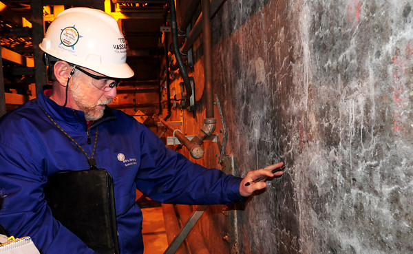 Seabrook: Ted Vassallo shows where water has seeped in to the concrete below ground, where the cable trays are run which carries electricity for the plant operations. Bryan Eaton/Staff Photo