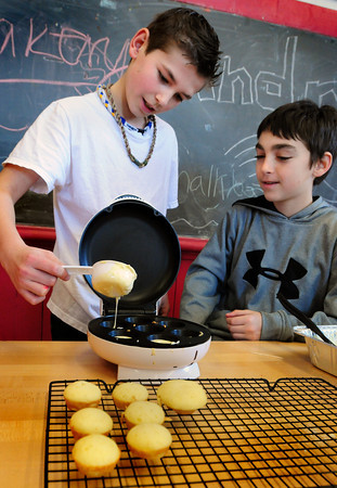 "Newburyport: Kenny Hodge, left, and Ryan Thibault, both 11, make cupcakes for a ""cupcake war"" vying with other teams for the best design. This month's was a pizza-themed contest at the Kelley School Teen Center. Bryan Eaton/Staff Photo"