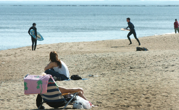 Salisbury: Sun-worshippers and surfers both were out enjoyed the summer-llike weather at Salisbury Beach on Monday. Higher than normal temperatures are forecast for the whole week. Bryan Eaton/Staff Photo