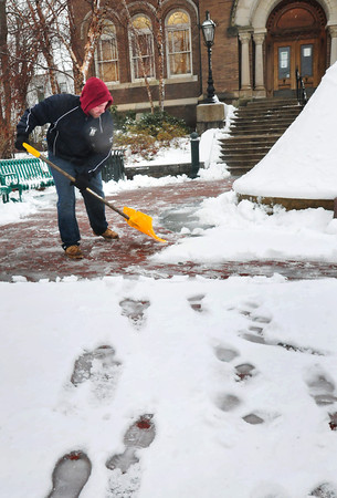 Amesbury: Ryan Ricci from the Amesbury DPW cleans up snow around the front of the public library yesterday morning. But downtown Newburyport was fairly empty of snow as an east wind in the first part of the day brought in warmer temperatures off the ocean. Bryan Eaton/Staff Photo
