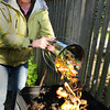 Newburyport: Nancy Roeder of Newburyport dumps kitchen scraps into her composter. Bryan Eaton/Staff Photo