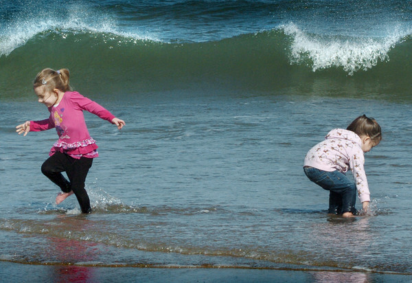 Salisbury: Temperatures close to 70 degrees brought scores of people to Salisbury Beach yesterday afternoon. Lillian Tyler, 4, runs out of the ocean as her friend Janelle Yeaton, 3, both of Haverhill splashes about. Bryan Eaton/Staff Photo