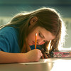 Salisbury: Chloe Hynes, 9, bathed in warm sunlight works on her math homework in the technology room at the Boys and Girls Club in Salisbury on Tuesday afternoon. Bryan Eaton/Staff Photo