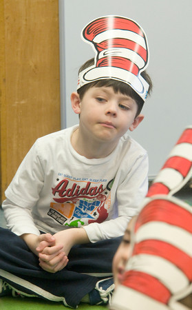 """Newburyport:Max Nolan, a student in Julie Carroll's kindergaten at the Brown School in Newburyport, listen as Cindy Johnson reads """" My Many Colored Day"""" by Dr Suess to his class.  A number of people from the community came by the school to read to students in celebration of Dr Suess's birthday. JIm Vaiknoras/staff photo"""