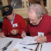 Amesbury: Veteran Leo Mione and Stuart Atkins sign legacy books for each other at a breakfast for World War 2 veterans and their families at the Hollow Cafe in Amesbury Friday morning. Jim Vaiknoras/staff photo