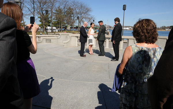 Newburyport: SPC Travis Souther and Marissa Games are married by Justice of the Peace Richard Jones in front of friend and family at Market Landing Park Friday. Travis is being deployed later this spring. Standing up for him is his Brother TJ Souther. JIm Vaiknoras/staff photo