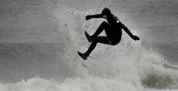 Salisbury: A surfer takes advantage of the high waves off Salisbury Beach as he catches some air while surfing Sunday afternoon. Jim Vaiknoras/staff photo