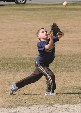 Newbury: Joe Abt, 8, show great form and consentration as he field a fly ball while plaing catch with his dad Brian on the Upper Green in Newbury Sunday afternoon. Jim Vaiknoras/staff photo