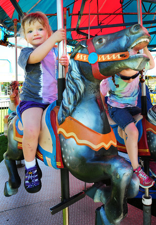 Amesbury: Lyla Travers, 3, of Merrimac rides the carousel with her cousin, Emma Matias, 4, lower right, of Goffstown, NH at the carnival near the Sparhawk School on Main Street in Amesbury on Saturday. The carnival was to raise money for Amesbury Days events. Bryan Eaton/Staff Photo