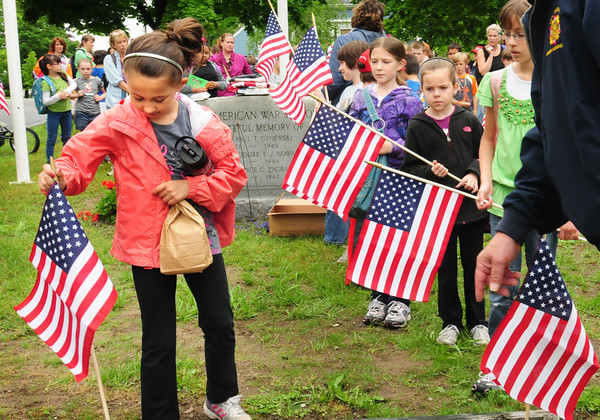 Amesbury: Grace Spanoghe, 9, places a flag at the Polish American War Memorial on Market Street in Amesbury under the direction of Bob Smith, commander of VFW Post 2016 on Wednesday. The students from the Amesbury Elementary School then went on to put flags on the graves of veteran's at the Mt. Prospect Cemetery. Bryan Eaton/Staff Photo