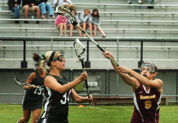 Newburyport: Newburyport's Julia Kipp passes the ball off over Manchester Essex player Taylor Coons. Bryan Eaton/Staff Photo