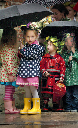 Newburyport: Wearing her crown of flowers, Madeleine Jackman peers out from her umbrella at the rain with Calvin Eaton and Isla Trail at the Newburyport Montessori School yesterday. They were lining up for their annual May Day celebration walking to Newburyport City Hall instead of Waterfront Park where the event has always been held. Bryan Eaton/Staff Photo