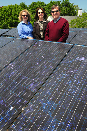 Newburyport: Standing amidst the solar panels on the roof of the Tannery Marketplace in Newburyport, from left, Molly Ettenborough, renewal energy coordinator for Newburyport and solar coaches Jill Haley Murphy and Ron Martino. Bryan Eaton/Staff Photo