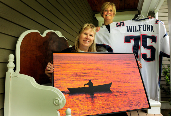 Amesbury: An antique-style deacons bench, a photo of Point Shore in Amesbury by elementary school teacher Billie McLane and a Patriot's shirt signed by Vince Wilfork are some of the items Sherrie Ziomek, left, and Patty Mellon are auctioning off. Bryan Eaton/Staff Photo