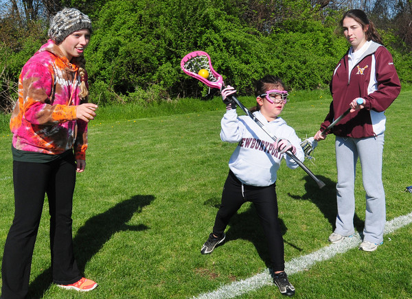 "Byfield: Newburyport High lacrosse players Morgan Timmerman, 15, left and Jillian Ouellette, 17, give pointers to Mia Philippino, 8, of Newburyport at Triton for a clinic ""Stick It To Cancer"" fundraiser. Bryan Eaton/Staff Photo"