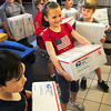 Newburyport: Ella Hartley, 6, surrounded by her classmates walk into the Newburyport Post Office yesterday afternoon carrying packages to send to troops in Afghanistan. The Brown School student body raised money for items such as toiletries and snacks and Diana Ouellette's class volunteered to deliver them via little wagons. Bryan Eaton/Staff Photo
