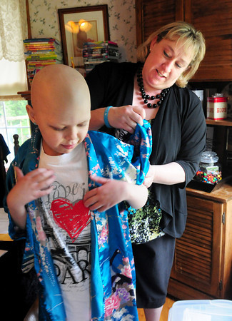 Merrimac: Tutor Kathy Terceiro helps Emma Jouneay with a kimono from Japan. Bryan Eaton/Staff Photo