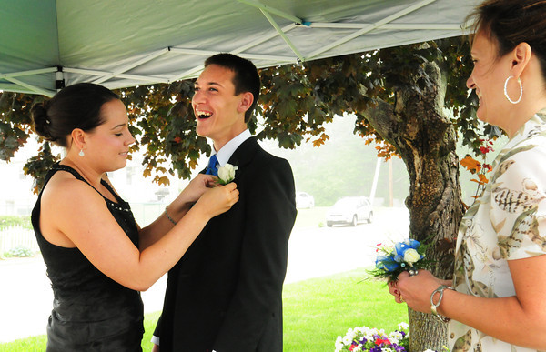 Salisbury: Sue Mitchell, right, looks on as Jess Reusch pins a corsage on Mitchell's son, Sean. Reusch, Sean's long time friend and running mentor, went with him to his Triton High School prom last night. Bryan Eaton/Staff Photo