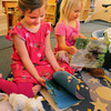Newburyport: Lily Pilz, 5, left, and Corinne Welling, 4, read books in their pajamas for Pajama Day on Tuesday at the Newburyport Montessori School. The curtains were pulled down and twinkling lights were hung in the ceiling. Bryan Eaton/Staff Photo