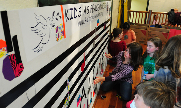 "Newburyport: Students in art class at the Bresnahan School in Newburyport use duct tape to create musical bars and scales for a Kids as Peacemakers poster. The theme of the poster to be used at the school's Memorial Day service is ""Peace is Music To Our Ears."" Bryan Eaton/Staff Photo"