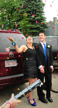 Salisbury: Jess Reusch, left, and Sean Mitchell get sprayed with a confetti cannon by his sister Kendall as they head to Mitchell's Triton High School prom last night. Bryan Eaton/Staff Photo