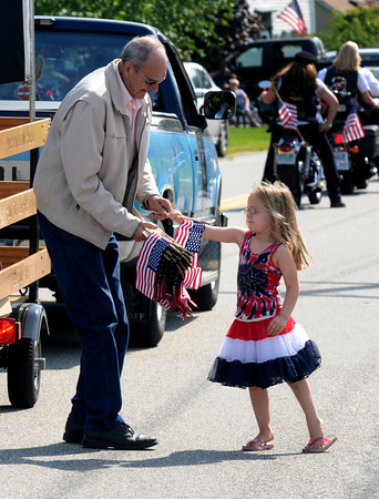 Seabrook: Joe Alexander hands a flag to Natalie Perkins, 4, as the annual Seabook Memorial Day Parade makes it's way down Walton Road Sunday morning. Jim Vaiknoras/staff photo