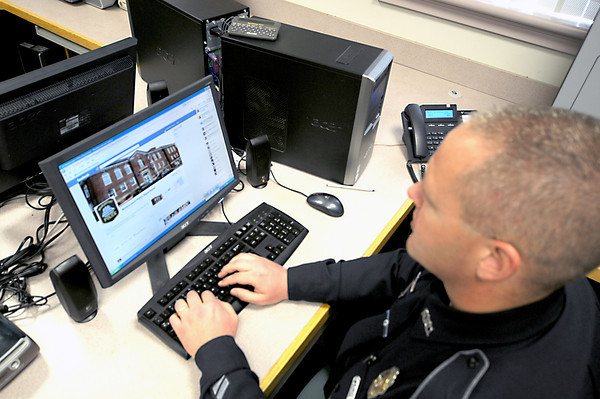 Newburyport: Officer Mathew Simons logs into eh new Newburyport Police Facebook page from the station Tuesday. Jim Vaiknoas/staff photo