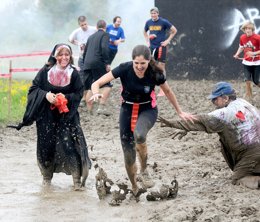 Amesbury: A runner bairly escapes the clutches of 2 zombies as she splashes through the mud at the Run for Your Lives Zombie 5k  at Amesbury Sports Park Saturday. Jim Vaiknoras/staff photo