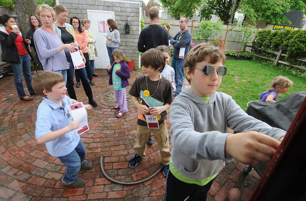 "Newburyport:Zach Guillow, 9, puts up flyer on a door knob promoting  ""Port Pride"" a group supporting approval of 2 school projects and a senior center., during a get together of supporters at Meghan Kinsey Newburyport home Jim Vaiknoras/staff photo"