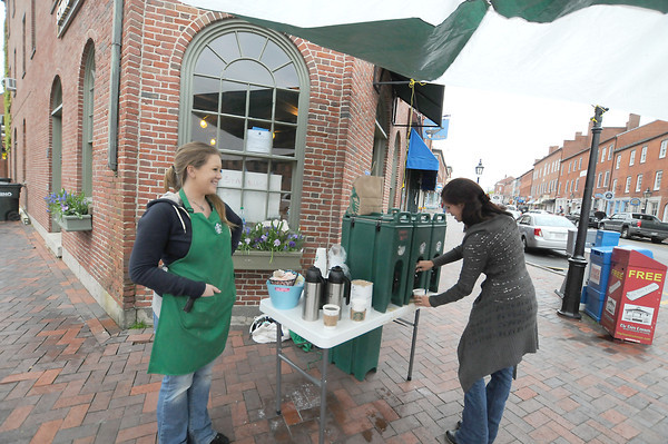 Newburyport: Starbuck's employees Meagan Guptill and Crystal Materkowski searve free coffee on State Street in Newburyport. The coffee shop is being renovated, so they are giving away their product to keep up with the caffeine fix of their customers. Jim Vaiknoras/staff photo