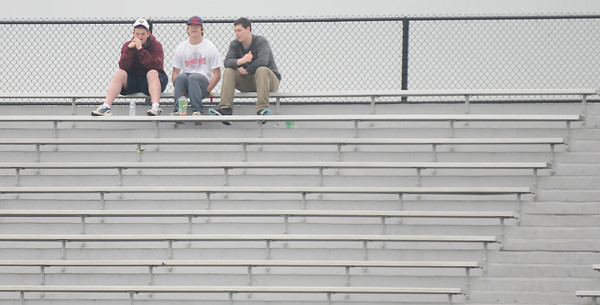 Newburyport: Three lacrosse fans cheer on the Clippers as Newburyport plays Lynnfield Wednesday on a wet cloudy afternoon at War Memorial Stadium in Newburyport. Jim Vaiknoras/staff photo