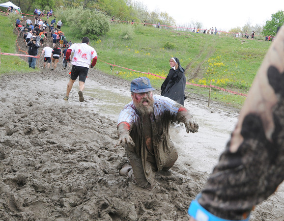 Amesbury:  One of the many zombie at the Run for Your Lives Zombie 5k  at Amesbury Sports Park Saturday reaches out from the mud to slow down a runner. Jim Vaiknoras/staff photo