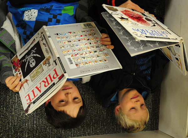 Amesbury: Drew Davis, 8, left, and Will Legg, 9, find a cozy spot from yesterday's blustery weather in the library at Amesbury Elementary School. The third-graders were read a book about Colonial America by librarian Cathy Patten, then got to choose a book to read for the rest of the period. Bryan Eaton/Staff Photo