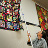 Amesbury: Jensi Rogers hangs a quilt by Ellen Vidal from the Chutes and Ladders class. Bryan Eaton/Staff Photo