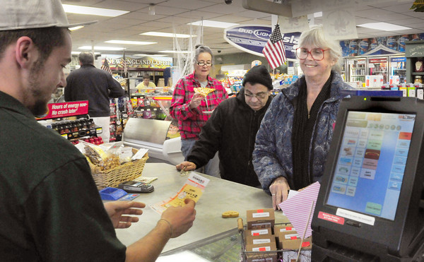 Seabrook: Christian Cook of O'Brien's General Store in Seabrook hands Carol LaFontaine her lotto picks yesterday afternoon as others wait in line for theirs. LaFontaine was driving from Maine to Florida and pulled off the highway to take her chances on the game now worth $500 million. Bryan Eaton/Staff Photo
