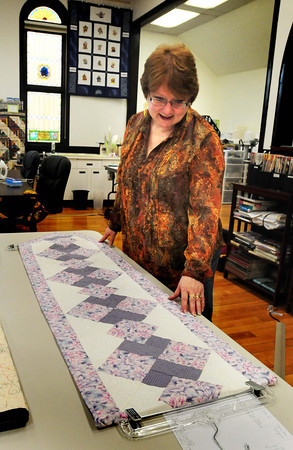 Amesbury: Carole Vogel arranges a piece by Ann Cummings from the Learn to Quilt class. Bryan Eaton/Staff Photo